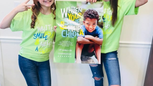 two girls pose for the camera holding a Smiles for Life poster, wearing lime green shirts and sunglasses