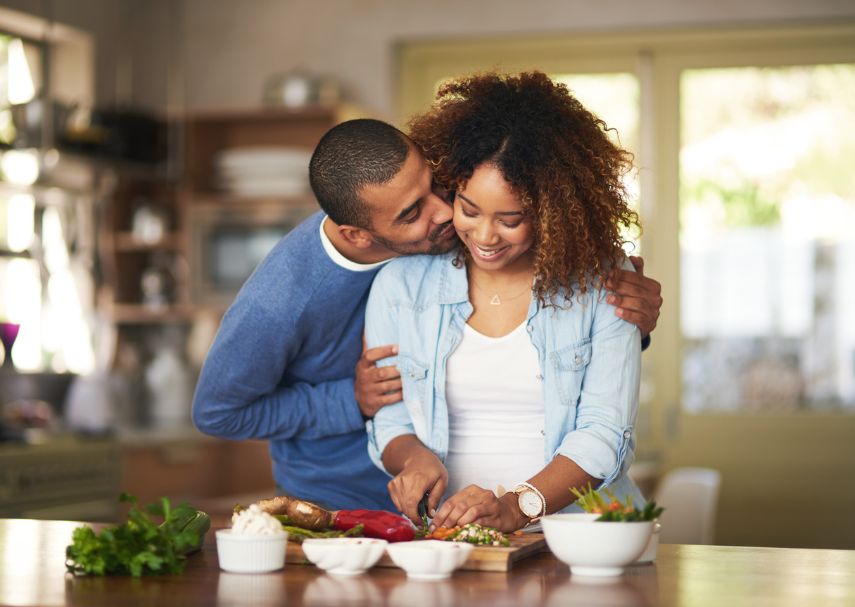 Shot of a young man kissing his wife while she prepares a healthy meal at home