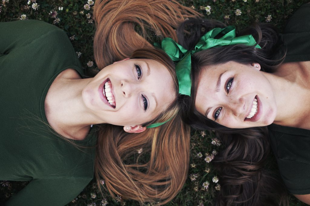 Two girls laying down on the grass laughing upwards towards the sky. It might be st. patricks day because of the green bows in their hair.